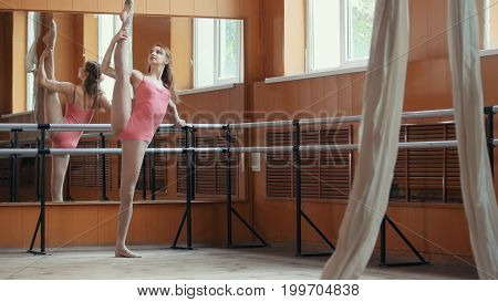 Beautiful girl shows amazing flexibility of the legs of the ballet bar, circus artist