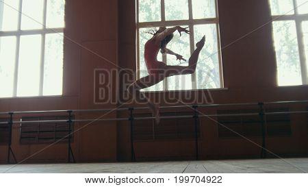 Ballerina performs acrobatics tricks in studio, slow-motion, circus artist - wide angle