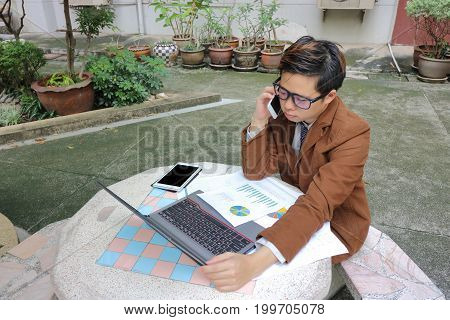 Handsome young business man talking on the phone with customer.