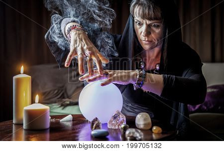 middle aged woman with reading fortune in candle light