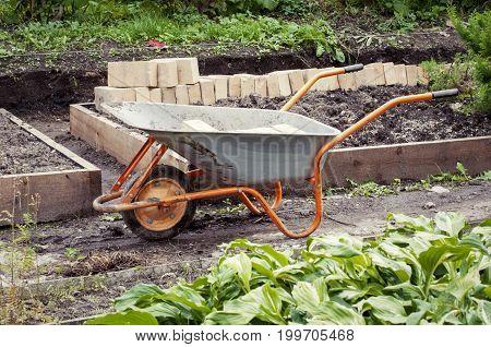Wheelbarrow In A Green Rural Garden