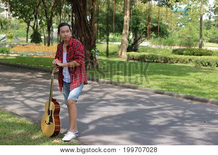 Portrait of guitarist relaxing against acoustic guitar in nature with copy space background.
