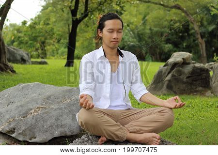 Young yogi man doing yoga meditation while sitting in lotus position on the rock in the park.