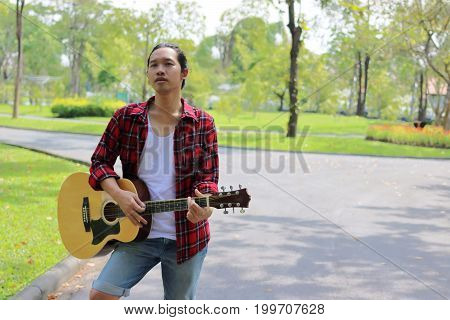 Portrait of guitarist playing music on acoustic guitar in the park background.