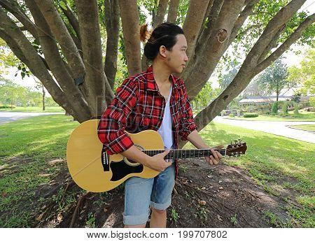 Wide angle shot of young relaxed man playing music on acoustic guitar in a beautiful nature background.