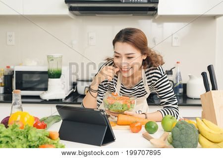 Smiling Vietnamese Woman Watching Tv Show On The Digital Tablet And Cooking Dinner In Home Kitchen