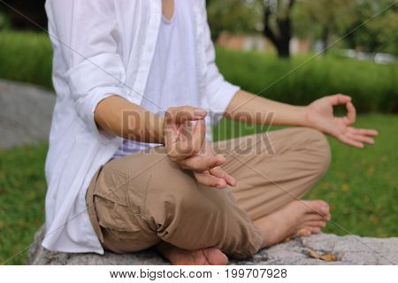 Close up hands of young yogi man doing yoga meditation while sitting in lotus position on the rock in the park.
