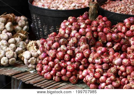 Group of red small red shallot on wooden bamboo shelf, organic freshness food ingredient, fresh market, onions, food ingredient for kitchen