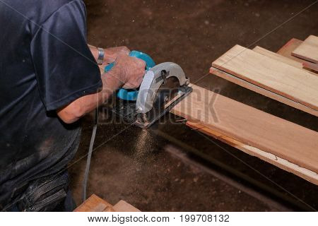 Aerial view of electric circular saw is being cut a piece of wood against hands of senior carpenter in carpentry workshop.