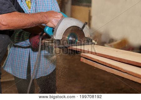 Side view of electric circular saw is being cut wooden board against hands of senior carpenter in carpentry workshop.