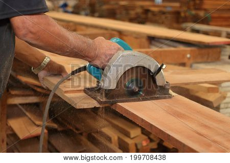 Close up hands of senior carpenter cutting a piece of wood against electric circular saw in carpentry woodshop. Woodworking concept