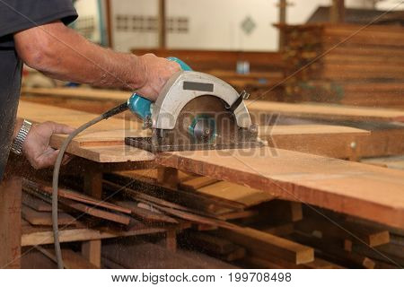 Hands of carpenter is working with a circular saw in carpentry workshop.