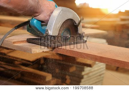 Electric circular saw is being cut a piece of wood by carpenter in carpentry workshop.
