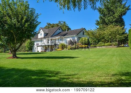 Big family house built on farm land. Image of residential house on sunny day framed by green lawn and tree leaves