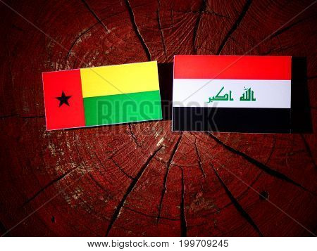 Guinea Bissau Flag With Iraqi Flag On A Tree Stump Isolated