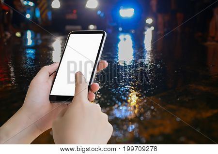 hand hold mobile blank screen and water on street and color lighting traffic night illuminated reflection liquidusing the car on the road when it weather rainy season accident copy space the right