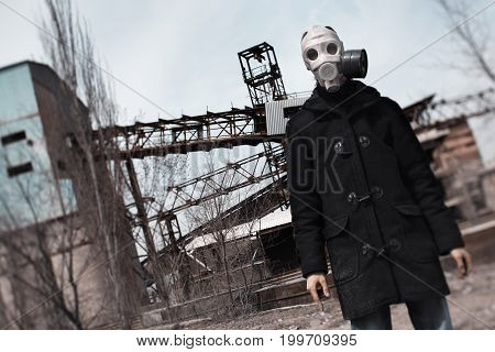 Man in gas mask standing at the factory after doomsday