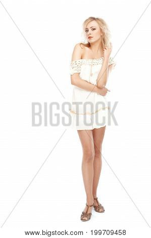 Blond woman in dress posing on a white background