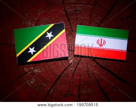 Saint Kitts And Nevis Flag With Iranian Flag On A Tree Stump Isolated