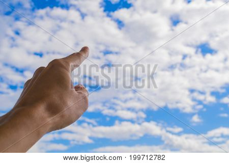 Left forefinger of human hand pointing to blue sky and white clouds.