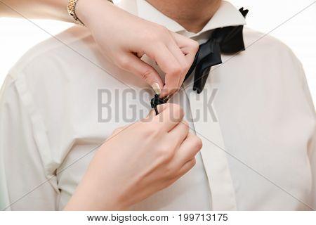 wedding ceremony groom preparations. bow tie help