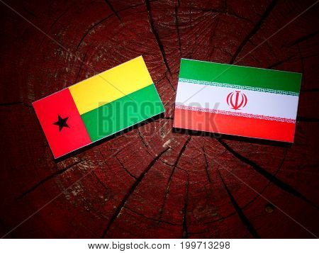 Guinea Bissau Flag With Iranian Flag On A Tree Stump Isolated