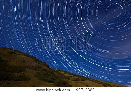 round startrail in the night with hill in foreground