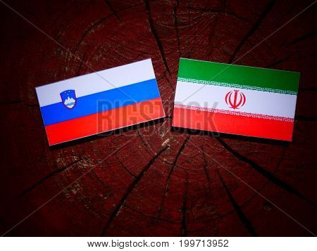 Slovenian Flag With Iranian Flag On A Tree Stump Isolated