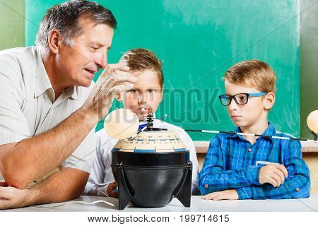 Two schoolboys and their teacher learning solar system in class at the desk against blackboard