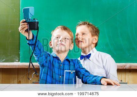 Two schoolmates make selfie at blackboard in school. Back to school concept background
