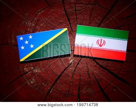 Solomon Islands Flag With Iranian Flag On A Tree Stump Isolated