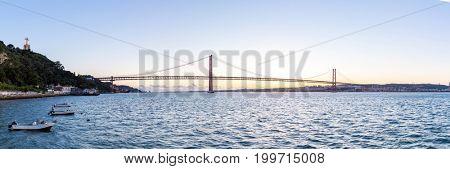 Lisbon cityscape with 25 de Abril suspension Bridge, Portugal at dusk Panorama