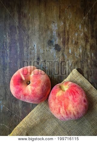 Fresh peaches on the wooden floor. In China Korea and Japan, the peach is a symbol of happiness, prosperity, immortality, and longevity. In Ancient Greece, the peach was the sacred fruit of the god of marriage.