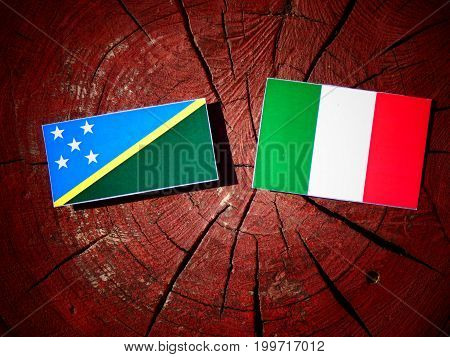 Solomon Islands Flag With Italian Flag On A Tree Stump Isolated