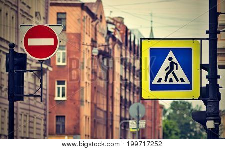the street sign or the road sign the crosswalk and the movement it is forbidden on the city street in the photo with effect of a retro.