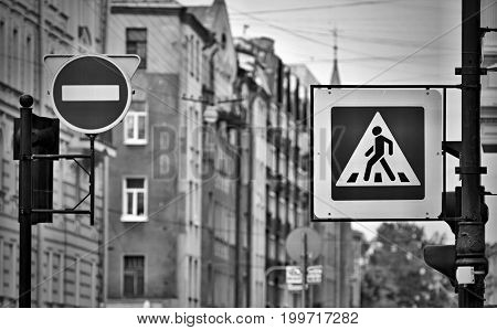 the street sign or the road sign the crosswalk and the movement it is forbidden on the city street in the photo with effect monochrome tone.