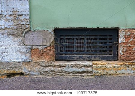 one window with an iron lattice to the cellar of the old house on the destroyed brick wall