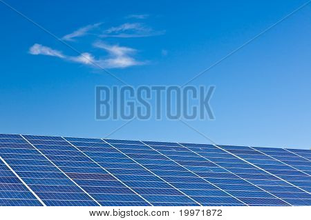 Photovoltaic panels in a solar power plant over a deep blue sky. poster