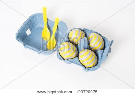 Foil covered chocolate easter eggs with plastic spoons in paper box on white background