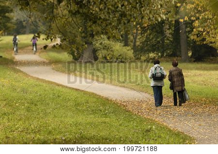 Two old ladies and two cyclists in the distance on autumn path - Unidentified people with their backs to the beholder