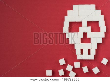 The skull made from sugar cubes. Sugar Kills. Red background. diabetes concept. Suggesting dieting concept. Unhealthy white sugar concept. Copy space. Space for text.