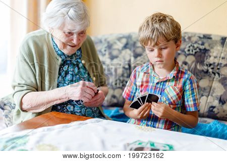 Active little preschool kid boy and grand grandmother playing card game together at home.