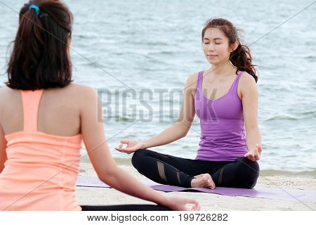 Young healthy women practicing yoga on the beach healthy lifestyles wellness well being