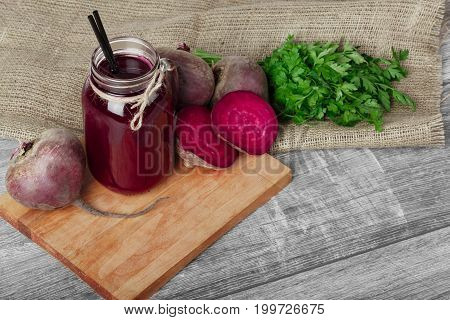 A top view of a mason jar of beetroot juice with straw on a wooden background. Whole and cut beetroots and fresh parsley on a fabric. A lot of healthy ingredients for cooking on a cutting board.