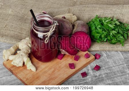 A view from above of a big mason jar of red beverage with straw and many organic ingredients on a cutting board and on a wooden background. Whole and cut beetroots, ginger and parsley on a fabric.