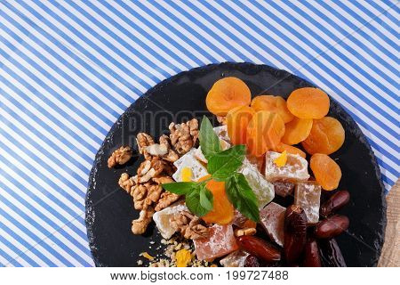 A close-up picture of a black plate with different confectionery ingredients on a striped fabric background. Orange dried apricots, nutritious walnuts, mint leaves, dry date fruits, turkish delight.