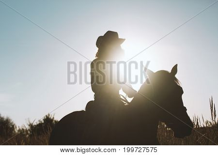 Silhouette of a woman in cowboy hat riding a horse - sunset or sunrise, horizontal, telephoto