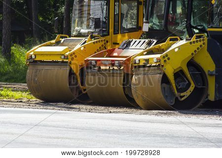 Three road rollers stand on the edge of the road against a background of green trees