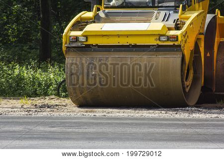 Road roller stands on the edge of the road against the background of green trees