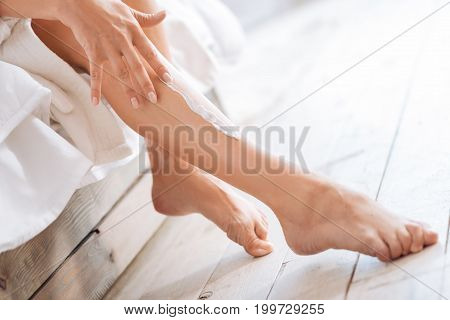 Moisten skin. Beautiful woman sitting on her bed after shower and using lotion while massaging legs